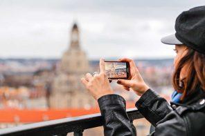 Eine junge Frau nimmt mit dem Smartphone ein Foto der Dresdner Frauenkirche auf.